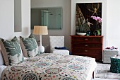 Double bed with country-house-style patterned bedspread and leaf-patterned scatter cushions in bedroom with ensuite bathroom