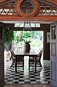 Wicker chairs and old wooden table on chequered tiles