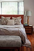 Bedroom with double bed, upholstered bedroom bench at foot of bed and bay window