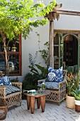 Korbstühle mit Batikkissen und afrikanischer Beistelltisch auf Terrasse mit Pflanztöpfen