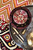Teller und Schale mit folkloristischem Muster auf Metall Tablett