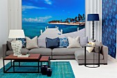 Set of coffee tables and grey sofa in front of mural wallpaper showing azure sky above tropical island
