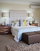 Bed with upholstered headboard flanked by symmetrical bedside cabinets in elegant bedroom in subdued colours