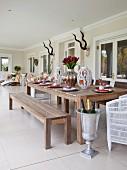 Überdachte Veranda mit langen, gedeckten Holztisch und Holzbank, eine Amphore aus Metall als Sektkühler