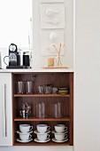Küchenunterschrank mit offener Tür und Blick auf Geschirr