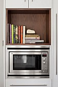 Microwave in kitchen cabinet below cookery books in wooden shelf compartment