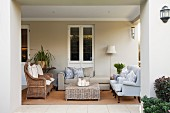 View from garden of loggia furnished with wicker armchairs and upholstered seating