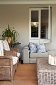 Loggia with wicker armchairs and modern sofa below open window