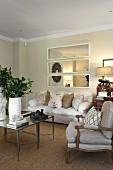 Sessel im Rokoko Stil neben Couchtisch, im Hintergrund Sofa mit Kissen, an Wand dreiteiliger Spiegel