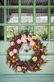 Wreath decorated with flowers and baubles on door