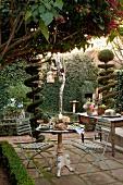 Festlich gedeckter Bistrotisch auf Terrassenplatz, im Hintergrund Buffet zwischen formgeschnittenen Bäumen im Garten