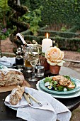 Salad, salmon and bread on festively decorated garden table