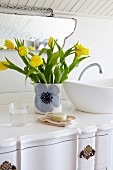 Vase of yellow tulips next to countertop basin on white washstand