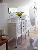 Vintage chest of drawers converted into washstand with twin countertop basins and cheval mirror in white bathroom