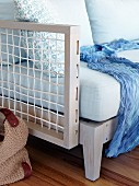 Designer sofa with wooden lattice frame and blue scarf on seat
