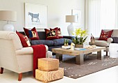 Rattan storage baskets next to upholstered furniture around rustic coffee table on rug in modern interior