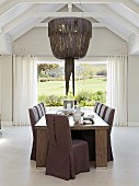 Chairs with purple loose covers in dining area below pendant lamp with leather lampshade and view through French windows