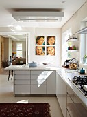 L-shaped kitchen counter with white base -unit fronts and open sliding door to one side