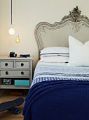 Bed with curved headboard painted pale grey, white and blue bed linen and matching bedside cabinet below simple pendant lamps