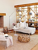 Wicker pouffe and chaise longue in front of wooden partition shelving
