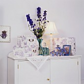 Lavender toile de jouy boxes; blue glass bottles and vase on white cabinet