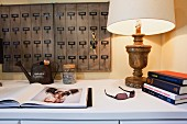 Close-up of lit lamp, key rack and books on table; California; USA