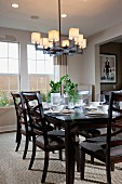 Wooden chairs around dining table below chandelier; Irvine; California; USA