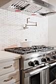 Kitchen with double gas stove below vent hood; Irvine; California; USA