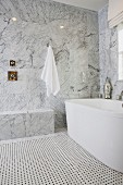 Bathroom with marble walls and bathtub; California; USA