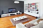 Helles Sofa und Couchtisch auf flokatiartigem Teppichläufer und Parkettboden, an dunkelgrauer Wand weisses Lowboard