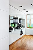 White fitted kitchen with parquet floor in modern interior with cardan lights integrated into ceiling