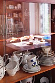 Traditional coffee services behind sliding glass doors of display cabinet