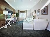 Sofakombination auf grauem, flokatiartigem Teppich gegenüber Arbeitsplatz mit Stehleuchte vor holzverkleideter Wand