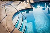 Kreisförmiger Einstieg in Pool mit Edelstahl Geländer auf Treppe