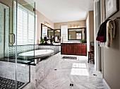 Eingebaute, ovale Badewanne hinter Glas Duschkabine in luxuriösem Bad mit Marmorboden