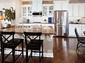 Stools arranged at breakfast bar in contemporary kitchen; San Marcos; California; USA