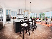 Stools arranged at breakfast bar in contemporary kitchen of open-plan house; Brea; California; USA