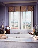 Baden mit Ausblick - vor Fenster eingebaute Badewanne mit Marmoreinfassung, auf Ablage Blumengestecke und Handtücher