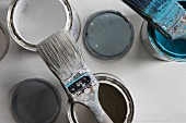 Flat paintbrushes with pale blue and light grey paint residue on open pots of paint