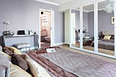 An double bed with a satin quilt and cushions in an elegant bedroom with a wardrobe with mirrored doors and an open door to the ensuite bathroom in the background