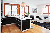Modern fitted kitchen with a breakfast bar with a view towards a leather sofa in an open, black-and-white living area with designer lamps