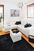 Decorative cushions on a white corner sofa in front of a patchwork leather rug in contrasting black