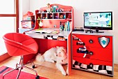 A dog lying underneath a red desk with a shelf attachment and a chest of drawers with racing car stickers
