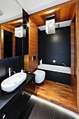 An elegant bathroom with a black and white bathtub and washstand, a wooden panelled toilet section and a modern lamp