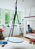 Child's bedroom with swing suspended from ceiling; child sitting on bunk beds and large window with garden view