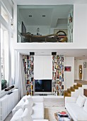 White sofa set and designer bookcases in living room, partly double-height; view of office in upper storey with glass wall