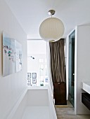 Modern bathtub below white spherical lamp in front of glass wall