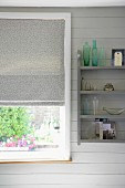 Collection of glass bottles on wall-mounted shelves on grey wooden wall in country-house-style interior next to window with Roman blind