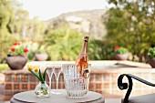 Blumenvase, Sektgläser & Sektflasche in Eiskübel auf Tisch im Freien