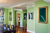 Cropped wooden dining table and chairs and paintings mounted on green walls; West Palm Beach; USA